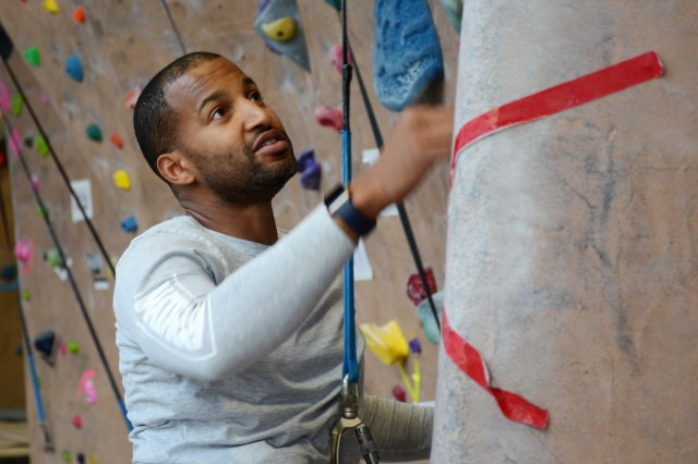 LIVERPOOL, N.Y. - Pfc. Raymond Piper, an Army Reserve combat medic from the 310th Military Police Battalion and a native of Bronx, N.Y., scales a rock climbing wall during a wounded warrior recreation therapy event in Liverpool, N.Y. Dec. 12.  The day-long trip, hosted by 3rd Battalion, 85th Mountain Infantry Warrior Transition Battalion, was a therapeutic event designed to provide wounded warriors the opportunity to conduct a physical activity while socializing with other wounded warriors.  (Photo by Warren W. Wright Jr., USA MEDDAC Fort Drum Public Affairs)