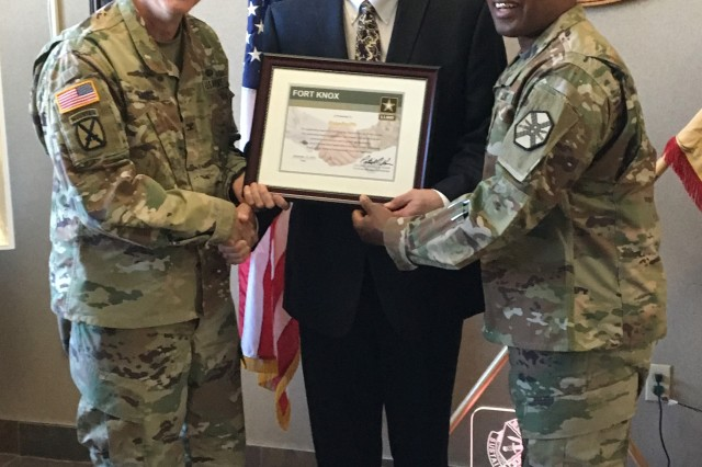 Vine Grove Mayor Blake Proffitt is presented with the Distinguished Fort Knox Teammate Award Dec. 12, 2018 by the Fort Knox Garrison Command team - Col. Pat Kaune and Command Sgt. Maj. Garrick Griffin.