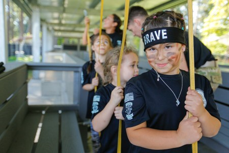 A child of a 1st Special Forces Group (Airborne) Soldier prepares to execute pre-jump commands at a mock aircraft, Aug. 29, 2018, during the 10th Annual Kid's Q-Course, Joint Base Lewis-McChord, Wash. The Kid's Q-Course was created in 2008 in order to allow Special Forces Soldiers to have a unique day of fun.