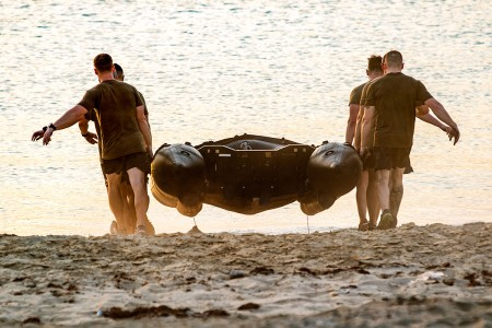 A team of U.S. Army Soldiers carry a Zodiac rigid inflatable boat during the 74th Engineer Dive Detachment's diver fitness challenge at Kuwait Naval Base, Kuwait, Aug. 31, 2018. The events of the diver fitness challenge are not exercises typically done by Soldiers in the U.S. Army, so they provide a unique opportunity for Soldiers to increase their capabilities by trying new challenges.
