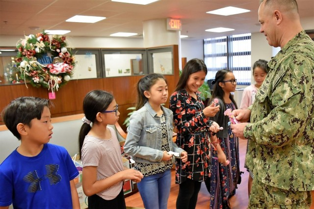 Capt. Raymond Batz, right, deputy commanding officer, Tripler Army Medical Center, gives student council leaders from Moanalua Elementary School memorabilia, and thanks them for donating Christmas ornaments to the hospital, at the Tripler command suite, Dec. 14.