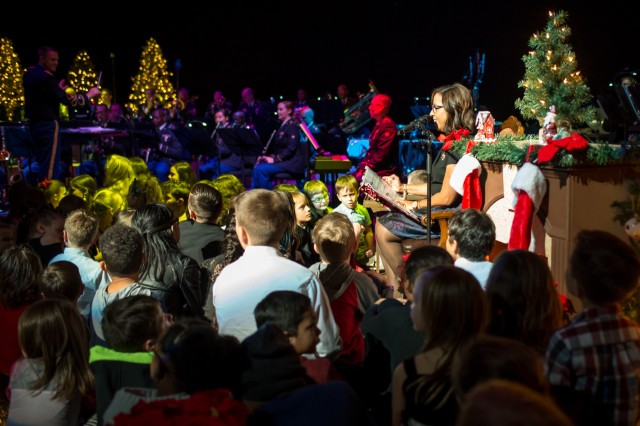 "COLUMBUS, Ga. (Dec. 17, 2018) - Michelle Brito, wife of MCoE and Fort Benning commanding general Maj. Gen. Gary M. Brito, reads the classic Christmas poem ""A Visit from St. Nicholas"" by Clement Clarke Moore. The Maneuver Center of Excellence Band from Fort Benning, Georgia, played a concert of classic and modern holiday music Dec. 15 at the RiverCenter for the Performing Arts in downtown Columbus, Georgia. (U.S. Army photo by Patrick Albright, Maneuver Center of Excellence, Fort Benning Public Affairs)"