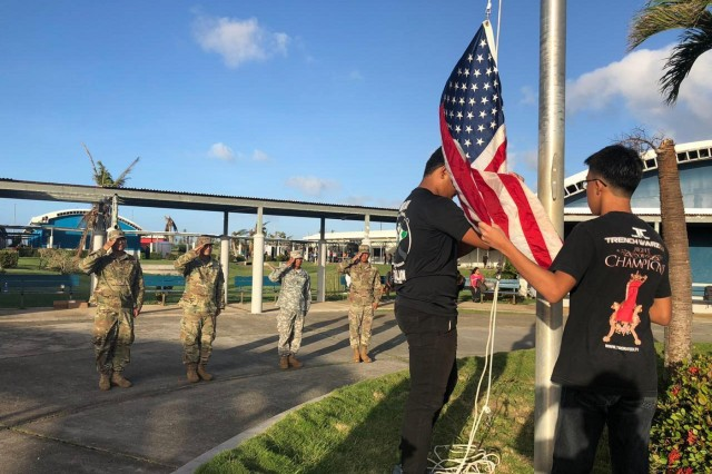 U.S. Army Reserve Soldiers with the 9th Mission Support Command and Soldiers with the Guam Army National Guard, currently assigned to Joint Task Group-Saipan, Task Force-West, present arms during the raising of the U.S. flag at Saipan Southern High School, Saipan, Commonwealth of the Northern Mariana Islands, Dec. 3, 2018. Students with the CNMI Public School System resumed classes after more than a month of no school due to the impact of Super Typhoon Yutu in late October. (Courtesy photo)