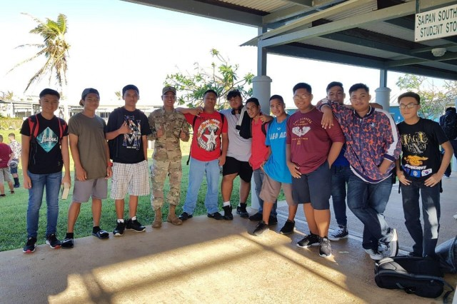 U.S. Army Sgt. Kenmark Orejola, fourth left, a Soldier and senior musician with the Guam Army National Guard, currently assigned to Joint Task Group-Saipan, Task Force-West, takes a photo with Saipan Southern High School students on Saipan, Commonwealth of the Northern Mariana Islands, Dec. 3, 2018. The students returned to school after more than a month without classes due to recovery efforts caused by Super Typhoon Yutu in late October this year. (Courtesy photo)
