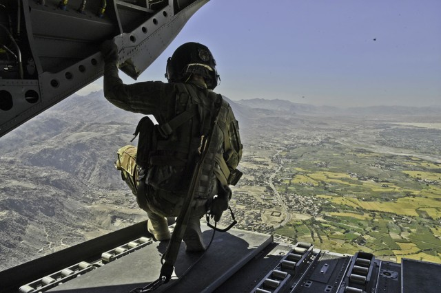 A CH-47 crew chief observes the terrain and air space of Afghanistan during a flight operation, Oct. 14 2018. As a CH-47 crew chief, he is responsible for air surveillance and attending to any in-flight maintenance.