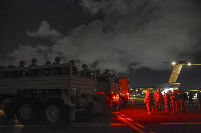 Soldiers are transported from the airfield to move to key facilities to provide support to civil authorities in the post hurricane training scenario. The quick reaction force has just arrived on a Mississippi National Guard C17 from Selfridge Air National Guard base in Michigan. Soldiers passing in the night before a dimly lit C17 from the 172nd Air Wing of the Mississippi National Guard, are arriving for a training exercise in the Virgin Islands to provide support to civil authorities in a post hurricane training scenario. In the early morning hours of December 13, Caribbean Thunder, and emergency deployment readiness exercise (EDRE) was initiated to validate the capability of the Michigan National Guard to notify, marshal and deploy a ready force of Michigan National Guard Soldiers to the Virgin Islands to provide support to the Virgin Islands National Guard and U.S. Virgin Islands Civil Authorities using a realistic scenario in a live and constructive training environment.
