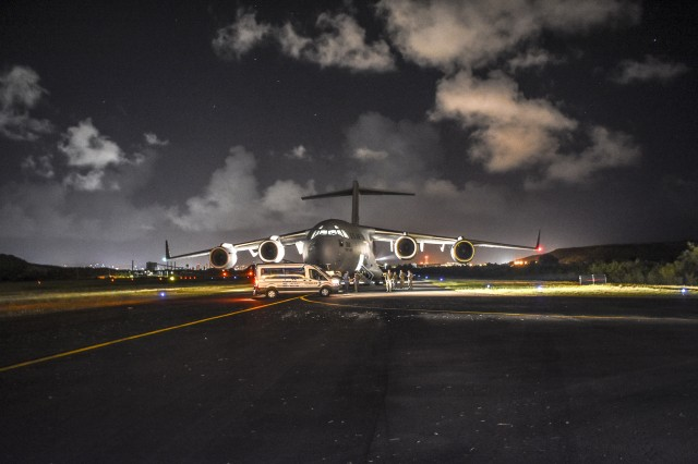 Soldiers passing in the night before a dimly lit C17 from the 172nd Air Wing of the Mississippi National Guard, are arriving for a training exercise in the Virgin Islands to provide support to civil authorities in a post hurricane training scenario. In the early morning hours of December 13, Caribbean Thunder, and emergency deployment readiness exercise (EDRE) was initiated to validate the capability of the Michigan National Guard to notify, marshal and deploy a ready force of Michigan National Guard Soldiers to the Virgin Islands to provide support to the Virgin Islands National Guard and U.S. Virgin Islands Civil Authorities using a realistic scenario in a live and constructive training environment.