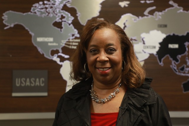 Stephanie Gilkes stands in front of a map of the combatant commands. The Security Assistance Command provides support to more than 6,000 cases, with a combined program value of over $192 billion, to 150 countries in the six COCOMs.