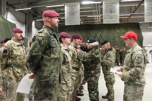 U.S., NATO ally, and partner service members receive Irish jump wings during a wing ceremony exchange hosted by the 5th Quartermaster Theater Aerial Delivery Company, at Rhine Ordnance Barracks, Kaiserslautern, Germany Dec. 14. The paratroopers earned their jump wings while participating in Operation Toy Drop, an annual multi-national training event designed to strengthen relations with the local community and develop interoperability.