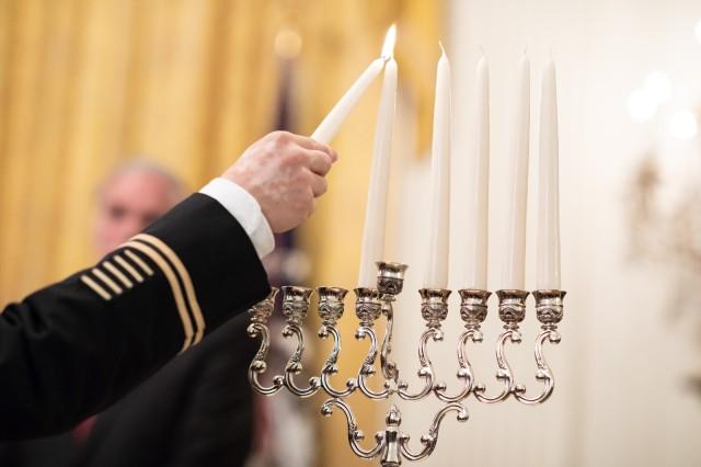 Col. Shmuel Felzenberg, 1st Inf. Div. senior chaplain, lights the Menorah during a Hanukkah reception Dec. 6, 2018, in the East Room of the White House.