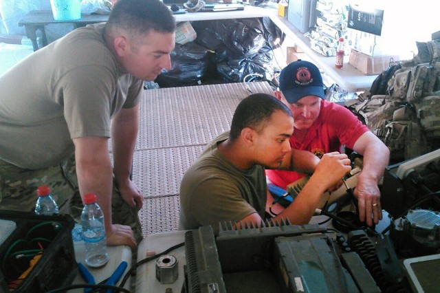Denny Caswell Logistic Assistance Representative, Army Field Support Battalion Germany, assists Sgt. Justin Romero (left) and Spec. Jason Graves, 277th Aviation Support Battalion, 10th Mountain Division, with setting up the Combat Service Support Very Small Aperture Terminal, in accordance with country specific requirements during Operation Atlantic Resolve, in Bulgaria, July 1, 2017.