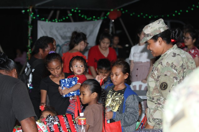 Children wait anxiously in line for their turn to receive their holiday gift handed out by U.S. Army Soldiers with the 9th Mission Support Command, U.S. Army Reserve, currently assigned to Joint Task Group-Saipan, Task Force-West, in partnership with the Office of Youth Affairs, Office of the Governor, at the Kagman Community Center, Saipan, Commonwealth of the Northern Mariana Islands, Dec. 15, 2018.