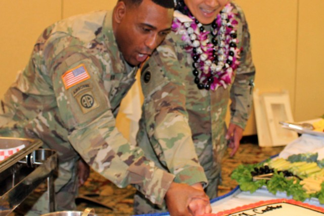599th Transportation Brigade Command Sgt. Maj. Rufus Lewis (left) and Col. Frazariel Castro, incoming 599th commander, slice into the welcome cake following Castro's change of command ceremony at brigade headquarters on Feb. 26.