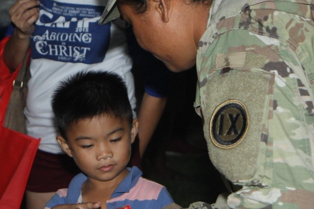 U.S. Army Spc. Mollie Atinisom, right, a Soldier with the 302nd Quartermaster Company, 9th Mission Support Command, U.S. Army Reserve, currently assigned to Joint Task Group-Saipan, Task Force-West, gives a holiday gift to a child at a holiday youth fair sponsored by the Office of Youth Affairs, Office of the Governor, at the Kagman Community Center, Saipan, Commonwealth of the Northern Mariana Islands, Dec. 15, 2018