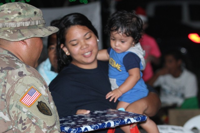 U.S. Army Staff Sgt. Cristin Duenas, left, a Soldier with the 302nd Quartermaster Company, 9th Mission Support Command, U.S. Army Reserve, currently assigned to Joint Task Group-Saipan, Task Force-West, gives a holiday gift to a mother and her child during a holiday fair sponsored by the Office of Youth Affairs, Office of the Governor, at the Kagman Community Center, Saipan, Commonwealth of the Northern Mariana Islands, Dec. 15, 2018.