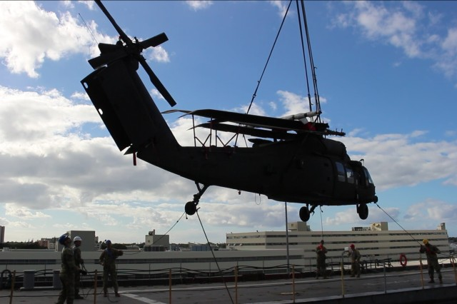 Transporters hold taglines to keep a Black Hawk helicopter steady in the trade winds as the ship's crane offloads it from the USNS Britten during port operations at Pearl Harbor on Dec. 17.