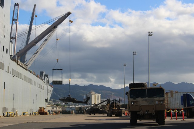Ships' cranes on the USNS Britten simultaneously offload a container and Apache helicopter from the USNS Britten during port operations at Pearl Harbor on Dec. 17.