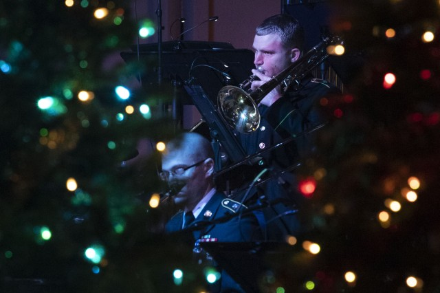 A member of the 282nd Army Band plays his instrument behind Christmas trees during the band's holiday concert at the Koger Center in Columbia, S.C. Dec.14.