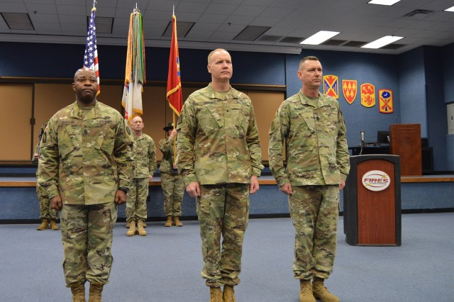 Outgoing Command Sgt. Maj. Finis Dodson, Brig. Gen. Brian Gibson, Army Air Defense Artillery School commandant and chief of ADA, and incoming Command Sgt. Maj. Stephen Burnley stand at attention during the ADA School change of responsibility ceremony Dec. 12, 2018, in Snow Hall at Fort Sill, Okla.