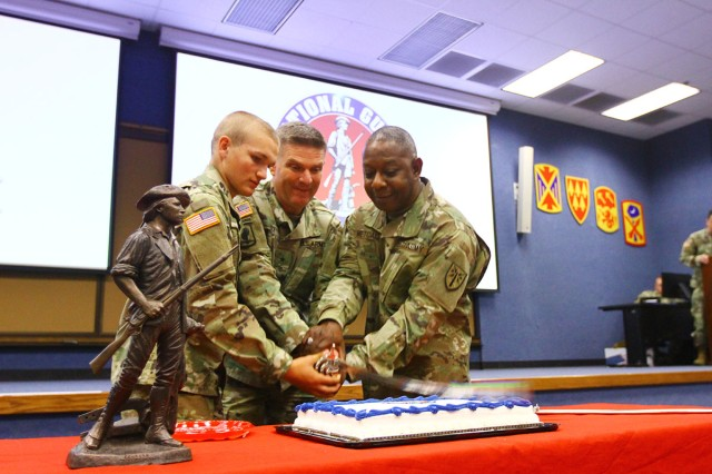 Fort Sill's youngest and oldest Army National Guard Soldiers cut the cake with Brig. Gen. Frank Rice (center), Fires Center of Excellence and Fort Sill Army National Guard Air Defense Artillery deputy to the commanding general, Dec. 13, 2018, in Snow Hall. On the left is Pvt. Dustin Ellis, age 17, who is a basic combat trainee in D Battery, 1st Battalion, 40th Field Artillery; and Chief Warrant Officer 5 Earnest Metcalf, FCoE senior warrant adviser for field artillery, 54, with 37 years of service.