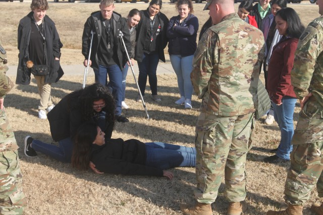 Milagro Trujillo, left, learns what a combat medic must do to move a casualty as she attempts to lift classmate Janet Herrera. Both are sophomores in The Health Academy at U.S. Grant High School in Oklahoma City who visited Fort Sill Dec. 12, 2018. Guiding them is Sgt. Benjamin Vanburen, Headquarters and Headquarters Battery, 30th Air Defense Artillery Brigade.