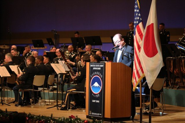"""Zama City Mayor Mikio Endo collaborates with the U.S. Army Japan Band, reading a poem as the band plays, during the sixth annual holiday concert, this year titled """"An American Christmas,"""" held Dec. 15 at Harmony Hall Zama."""