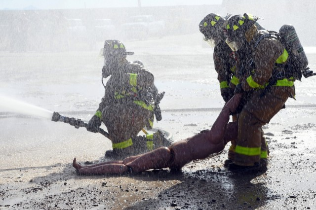 Two Army National Guard firefighters use the two-man arms carry casualty drag on a mannequin while another firefighter maintains flame suppression during the units' daytime portion of their search and rescue training exercises conducted at White Sands Missile Range, New Mexico, Dec. 19, 2018. The National Guard firefighter detachments have been taking part in their military rehearsal and validation exercises in order to augment their readiness posture for their upcoming mobilizations to Eastern Europe.