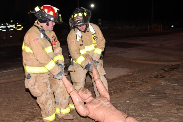 Two Army National Guard firefighters use the two-man arms carry on a mannequin during the units' nighttime portion of their search and rescue training exercises conducted at White Sands Missile Range, New Mexico, Dec. 19, 2018. The National Guard firefighter detachments have been taking part in their military rehearsal and validation exercises in order to augment their readiness posture for their upcoming mobilizations to Eastern Europe.