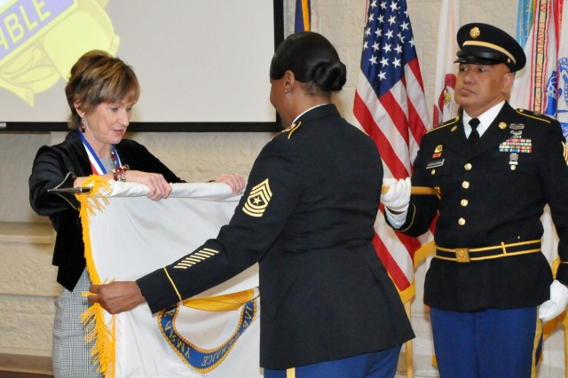 Rhonda VanDeCasteele, Joint Munitions Command, Deputy to the Commander, furls her Senior Executive Service flag to represent her retirement with assistance from Sgt. Maj. Shontina Edwards and Sgt. 1st Class Sefo Luafalemana, during her official retirement ceremony at the Rock Island Arsenal, Dec. 20.