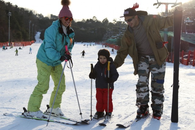 HONGCHEON, Republic of Korea - Staff Sgt. Ruben F. Fernandez, Madill, Oklahoma native, career counselor, Headquarters and Headquarters Battalion, 2nd Infantry Division/ROK-U.S. Combined Division, and spouse Adriana Fernandez, guide their seven-year-old son Adrian down a beginner-ski slope during a Strong Bonds family training event at Vivaldi Park Ski World Dec. 18-20. The event, open to both single and married Soldiers, focused on building ready families and strengthening trust through a series of lectures, presentations, group exercises, and conquering the slopes.