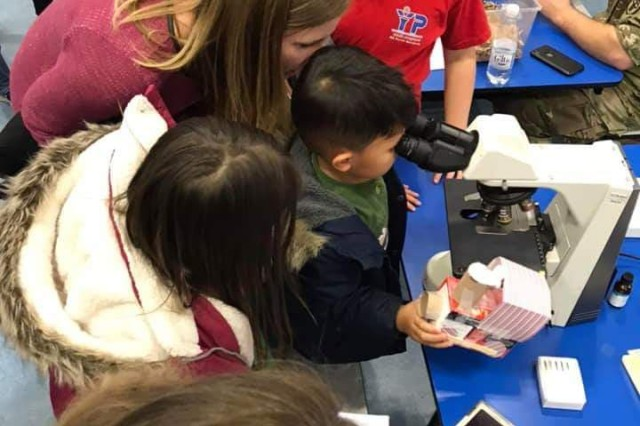 Ramstein Intermediate School students check out PHCE's Laboratory Science program's microscope during the school's STEAM Literacy night.