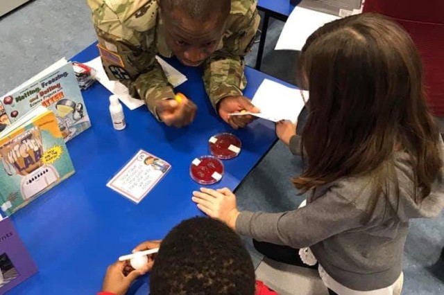 Staff Sgt. Kokou Bocovo, Noncommissioned Officer in Charge of PHCE�s Laboratory Science, shows students from Ramstein Intermediate School how many germs are still on their hands after washing them.
