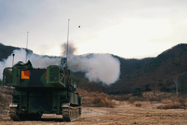 """CAMP HOVEY, Republic of Korea - A M109A6 Paladin fires a 155 mm inert training round during the 4th Battalion, 1st Field Artillery Regiment """"Defender,"""" 3rd Armored Brigade Combat Team, 1st Armored Division (Rotational) Table VI Gunnery at St. Barbara Range Dec. 5. Table VI Gunnery is an annual training requirement for Field Artillery units that certify individual howitzer crews and platoon Fire Direction Centers. This training focuses on overall readiness and maintaining Field Artillery core competencies at the section level. (U.S. Army photo by 1st Lt. Sean M. Kealey)"""