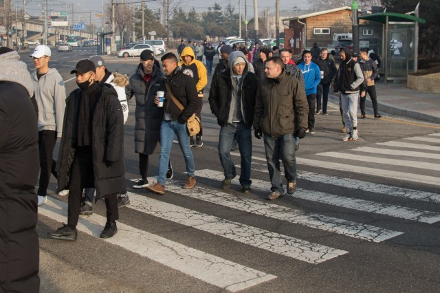 Soldiers with 210th Field Artillery Brigade, 2nd Infantry Divison/ROK-U.S. Combined Division, walk across a street near U.S. Army Garrison Camp Casey on their way to help citizens of the local community in Dongducheon City, Gyeonngi Province Dec. 21. The 210th FAB delivered charcoal to help disadvantaged families heat their homes during the winter season.