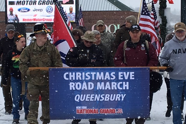 Retired New York Army National Guard Sgt. 1st Class Arthur Coon, center in red jacket, steps off for the 15th annual Christmas Eve Road March in Glens Falls, N.Y., December 24, 2018. Coon is joined by Mr. Kevin Tucker, at right, and Vermont Army National Guard Spc. James Kassebaum, left, holding the road march banner. Coon has organized the annual event to honor deployed service members since 2004 when Soldiers from the New York Army National Guard were deployed to Iraq.