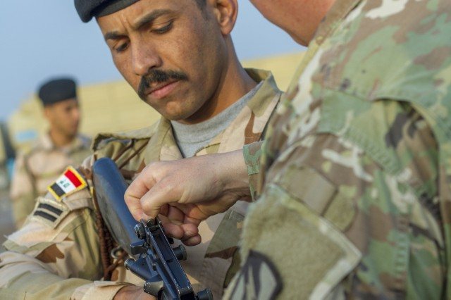 U.S. Army Sgt. 1st Class Michael Garner, right, security forces platoon sergeant assigned to Task Force India Bravo, teaches an Iraqi army primary marksmanship instruction course at Camp Taji, Iraq, Dec.19.