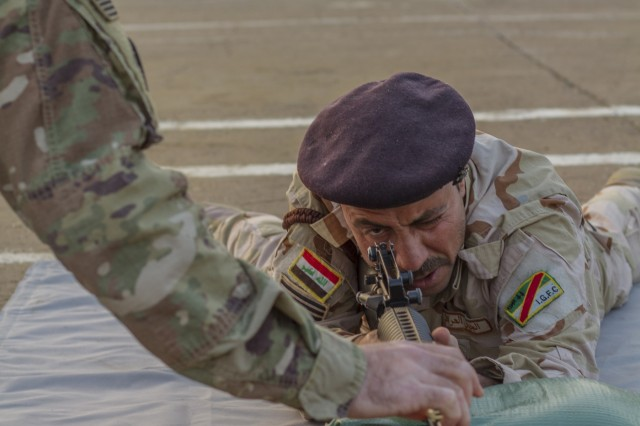 U.S. Army Spc. Matthew Driskill, left, a cavalry scout assigned to Task Force India Bravo, assists an Iraqi soldier with a dime/washer drill as part of a primary marksmanship instruction course at Camp Taji, Iraq, Dec.19. Task Force India Bravo is comprised of Soldiers from 1st Squadron, 98th Cavalry Regiment, 106th Support Battalion and 2nd Battalion, 114th Field Artillery Regiment, 155th Armored Brigade Combat Team, Mississippi Army National Guard, and is deployed in support of Combined Joint Task Force - Operation Inherent Resolve, working with the Iraqi Security Forces to develop a sustainable and inclusive force that can secure its sovereign borders, protect the population, and ensure the lasting defeat of ISIS.