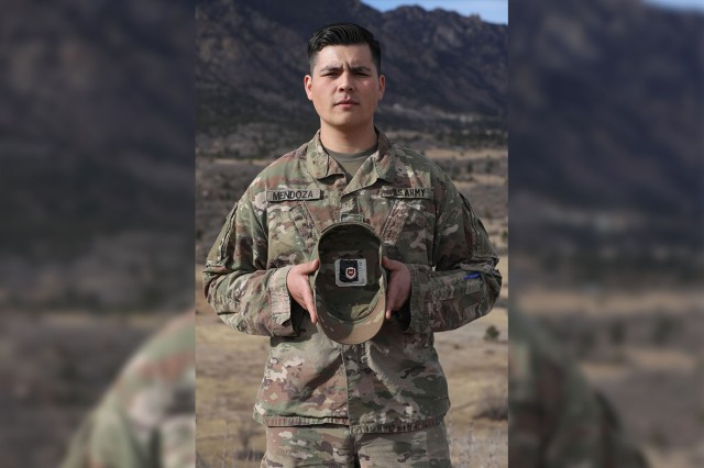 """Spc. Flavio Mendoza, assigned to the 22nd Human Resources Company, 4th Special Troops Battalion, 4th Sustainment Brigade, 4th Infantry Division, holds up his patrol cap showing his engineer crest tucked inside. """"I still carry the engineer crest in my (patrol cap). It lets me know where I came from, and that gives me pride,"""" said Mendoza. """"Even though I'm away and in a new career field, I will always be an engineer."""""""