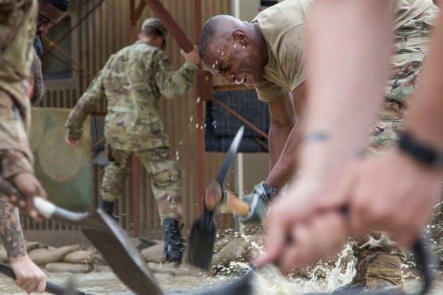 A Soldier uses a pickaxe to dig a trench to divert flood waters away from a barracks building at Camp Arifjan, Kuwait, Nov. 15, 2018. Soldiers from multiple units joined together to respond to the flooding in order to protect their living quarters.