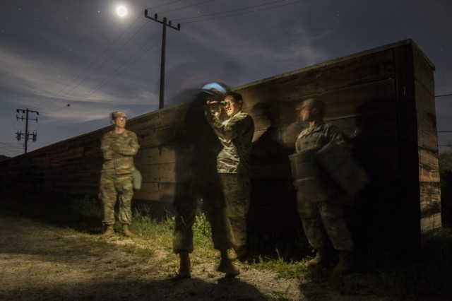 Under the light of a full moon, U.S. Army Soldiers, assigned to 2nd Infantry Division, 2nd Sustainment Brigade, use a night vision device to supervise crews during night gunnery qualifications near Warrior Base, South Korea, on Sept. 18, 2018. Vehicle crew evaluators (VCE) were present to offer feedback on crew duties, and to make sure each crew could be properly certified on their gunnery tables. (U.S. Army Photo by Spc. Adeline Witherspoon, 2nd Sustainment Brigade)