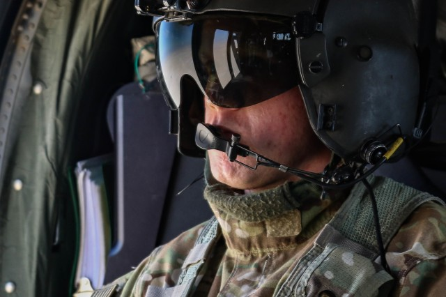 U.S. Army Sgt. Bradley Deraas, a UH-60L Black Hawk helicopter crew chief assigned to C. Company, 2-211th General Support Aviation Battalion, Minnesota Army National Guard, surveys the terrain during an aeromedical evacuation rehearsal at Camp Buehring, Kuwait, Dec. 11, 2018.  The rehearsal was conducted to prepare for Operation Desert Observer II, a combined arms live-fire exercise with Task Force Spartan and the Kuwaiti Land Forces, to validate protocols and strengthen communications between the ground teams and aviation assets.