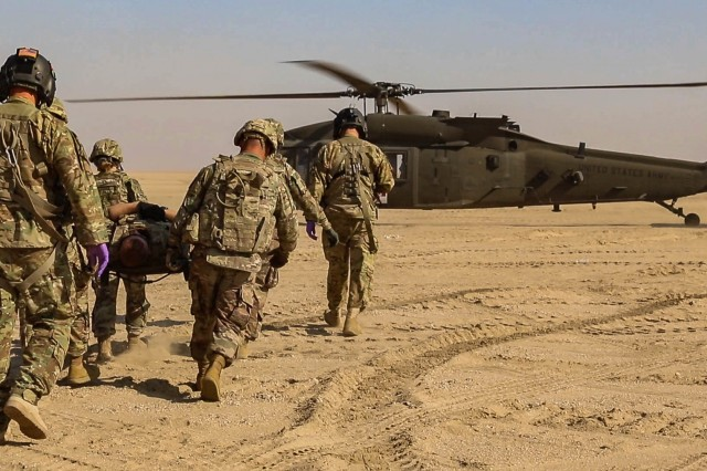 U.S. Army Soldiers assigned to the 2-211th General Support Aviation Battalion, Minnesota Army National Guard, and the 155th Armored Brigade Combat Team, Mississippi Army National Guard, carry a patient to a UH-60L Black Hawk helicopter during an aeromedical evacuation rehearsal at Udairi Range Complex near Camp Buehring, Kuwait, Dec. 11, 2018.  The rehearsal was conducted to prepare for Operation Desert Observer II, a combined arms live-fire exercise with Task Force Spartan and the Kuwaiti Land Forces, to validate protocols and strengthen communications between the ground teams and aviation assets.
