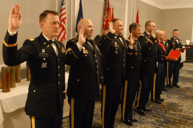 The 2018 Virginia National Guard inductees of the Honorary Order of Saint Barbara are sworn in before being awarded the Saint Barbara medallion Dec. 8, 2018, in Williamsburg, Virginia. The Honorary Order of Saint Barbara recognizes those who have demonstrated the highest standards of integrity, moral character, professional competence and contributed to the promotion of field artillery.(U.S. Army National Guard photo by Maj. Scott Drugo)