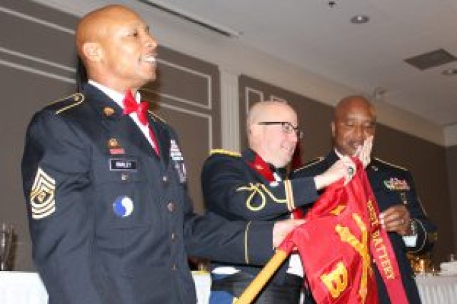 Lt. Col. Shawn Talmadg, commander of 1st Battalion, 111th Field Artillery Regiment, 116th Infantry Brigade Combat Team, and Command Sgt. Maj. Stanley Mosley, command sergeant major of the 1-11th, present 1st Sgt. Ricky Barley of Bravo Battery with the Best Battery streamer Dec. 8, 2018, in Williamsburg, Virginia. The streamer is awarded to the unit which demonstrates excellence throughout the training year in areas such as weapons qualification, physical fitness, drill attendance, tactical proficiency, and overall operations. (U.S. Army National Guard photo by Maj. Scott Drugo)