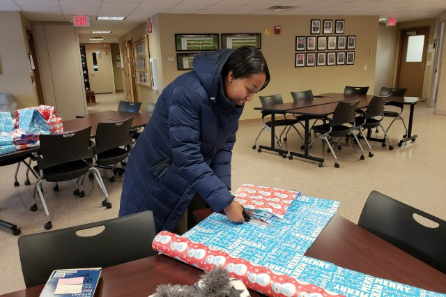 Summer Wilson wraps a gift as part of a donation by members of the 925th Contracting Battalion and Mission and Installation Contracting Command-Fort Drum, New York, who teamed with a local charity to adopt a family during Christmas.