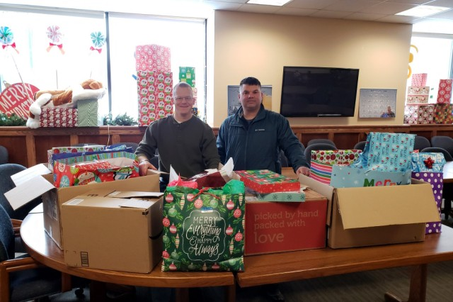 Lt. Col. Jessie Griffith, left, and Sgt. Maj. T.J. Higgs deliver gifts to the Watertown Urban Mission, a local charity that helps community members rise above their current circumstances through social outreach programs. Griffith is the commander of the 925th Contracting Battalion and Higgs is the battalion sergeant major.
