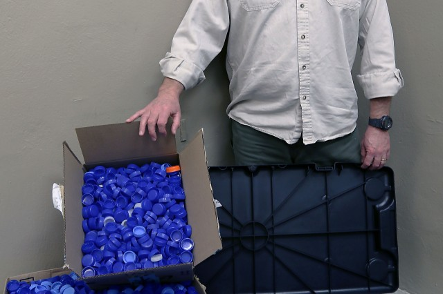 Thomas Luft, a Department of Defense civilian employee deployed as a contract analyst, Area Support Group, Bagram Airfield, Afghanistan, displays the bottle caps he has collected and will soon mail to St. Joseph Catholic Church in Huntsville, Alabama, to help needy school children. (Photo by Jon Micheal Connor, Army Public Affairs)