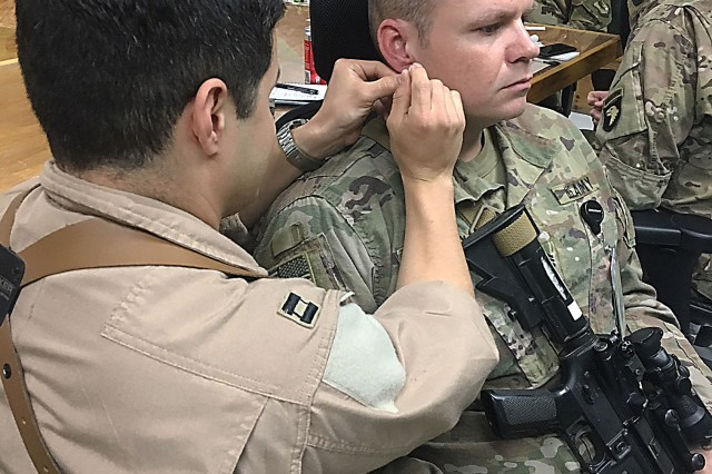 Air Force Capt. Christopher Sandoval places a needle in the outer ear of Army Sgt. 1st Class David Ussery during a four-hour Battlefield Acupuncture class given Nov.18 at Craig Joint Theater Hospital certifying an additional 12 providers. The course entailed a lecture/background session followed by practical application along with a written examination. (Photo by Dr. (Capt.) Carl Bryce, Craig Joint Theater Hospital)
