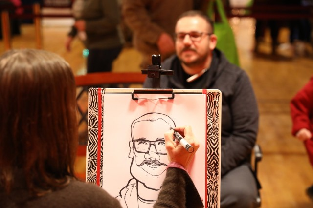 """A local artist draws a caricature for a guest during the annual Fort Carson tree lighting ceremony at the William """"Bill"""" Reed Special Events Center, Fort Carson, Colo., Dec.6, 2018. The free event, which kicked off the holiday season on post, included holiday songs by the 4th Infantry Division Band, free kids' activities, a winter gear and apparel sale, and Santa photos. (U.S. Army photo by Sgt. Daphney Black)"""