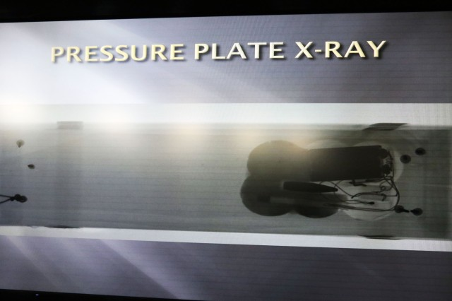 X-rays are taken of all evidence in Triage to ensure no hazards such as Trojan horses are observed. This x-ray shows a pressure plate containing a hazard.
